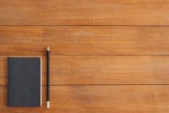 Предпосылка деревянного стола стола офиса с насмешкой вверх по тетрадям и карандашу и заводу Стоковые Изображения