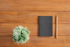 Предпосылка деревянного стола стола офиса с насмешкой вверх по тетрадям и карандашу и заводу Взгляд сверху с космосом экземпляра, Стоковые Изображения