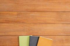 Предпосылка деревянного стола стола офиса с насмешкой вверх по тетрадям Взгляд сверху с космосом экземпляра Стоковое Изображение RF