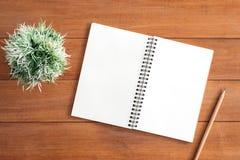 Предпосылка деревянного стола стола офиса с открытой насмешкой вверх по тетрадям и ручкам и заводу Стоковые Изображения