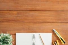Предпосылка деревянного стола стола офиса с открытой насмешкой вверх по тетрадям и ручкам и заводу Стоковое Фото