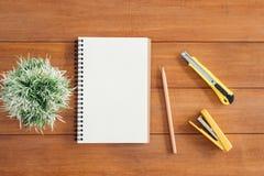 Предпосылка деревянного стола стола офиса с открытой насмешкой вверх по тетрадям и ручкам и заводу Стоковые Изображения RF