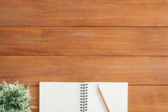 Предпосылка деревянного стола стола офиса с открытой насмешкой вверх по тетрадям и ручкам и заводу Стоковые Фотографии RF