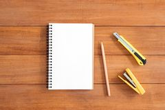 Предпосылка деревянного стола стола офиса с открытой насмешкой вверх по тетрадям и ручкам и заводу Стоковое Изображение