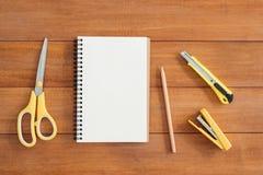 Предпосылка деревянного стола стола офиса с открытой насмешкой вверх по тетрадям и ручкам и заводу Стоковое Изображение RF