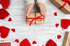 Предпосылка дня Валентайн Женские руки держа подарок дня валентинок над деревянным столом с красными сердцами Взгляд сверху Wrapp Стоковое Фото