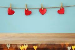 Предпосылка дня Валентайн сердца вися перед деревянной предпосылкой фон дисплея продукта Стоковая Фотография