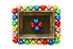 Предпосылка дня валентинок с красочной формой сердца шоколадов и рамка золота от взгляд сверху Стоковая Фотография