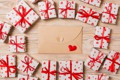 Предпосылка дня Valentines романтичная карта конверта с подарочными коробками и сердце на деревянной предпосылке стоковое изображение