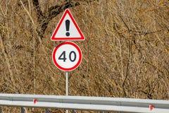 Предпосылка дорожных знаков опасности кустов вперед и ограничения в скорости 40 Стоковые Изображения