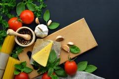 Предпосылка еды, ингридиенты для варить обедающий спагетти, овощи, соусы и специи, темная предпосылка скопируйте космос Взгляд св стоковые изображения