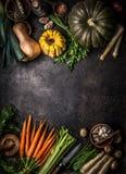 Предпосылка еды осени сезонная с красочными различными тыквами и органическими овощами фермы на темном кухонном столе, взгляде св стоковые изображения rf