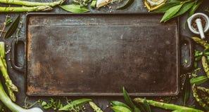 Предпосылка еды с открытым космосом для текста Травы, оливковое масло, специи вокруг литого железа жаря доску Взгляд сверху Стоковое фото RF