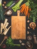 Предпосылка еды с разделочной доской и различные органические овощи фермы на темной деревенской таблице с утварями кухни, травами стоковое изображение