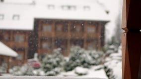Предпосылка запачканная зимой Деревянные коттеджи в горном селе во время сильного снегопада с coniferous вечнозеленым ландшафтом сток-видео