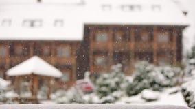 Предпосылка запачканная зимой Деревянные коттеджи в горном селе во время сильного снегопада с coniferous вечнозеленым ландшафтом акции видеоматериалы