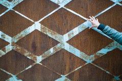 Предпосылка заржаветого винтажного металла с ромбовидным узором и винтажной голубой краской и худенькой открытой женской рукой Стоковые Фото
