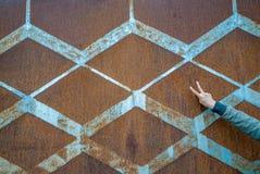 Предпосылка заржаветого винтажного металла с ромбовидным узором и винтажной голубой краской и худенькой женской рукой делая знак  Стоковые Фотографии RF