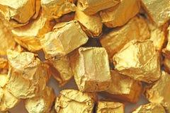 предпосылка золотистая Слитки или наггеты червонного золота Листовое золото te Стоковые Изображения