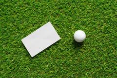 Предпосылка и шар для игры в гольф белой бумаги на зеленой траве поля для гольфа стоковое изображение rf