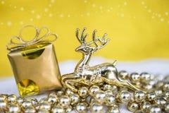Предпосылка концепции рождества сияющих северного оленя и подарочной коробки золота Стоковые Изображения