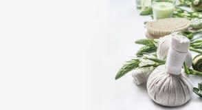 Предпосылка курорта с шариками массажа травяными, зелеными травами и цветками на белизне Красота, здоровая забота тела Стоковое Фото