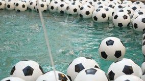 Предпосылка много черно-белой футбольных мячей Шарики футбола плавая в чисто воде Один шарик падает в воду акции видеоматериалы
