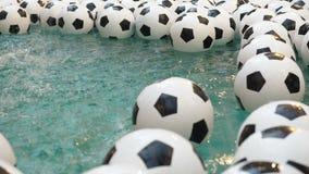 Предпосылка много черно-белой футбольных мячей Шарики футбола плавая в чисто воде Двигатели воды падают сверху акции видеоматериалы