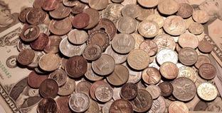 Предпосылка монеток лежа на бумажных банкнотах Соединенных Штатов Стоковое фото RF