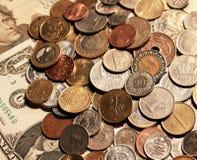 Предпосылка монеток лежа на бумажных банкнотах Соединенных Штатов Стоковые Фото