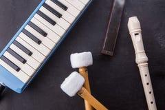 Предпосылка музыкальных инструментов с каннелюрой, pianika, губной гармоникой, и басовой ручкой на черное деревянном стоковое фото rf