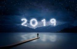 Предпосылка Нового Года, положение молодого человека на моле в озере и смотреть к горам под темным небом с пасмурным текстом 2019 стоковые фотографии rf