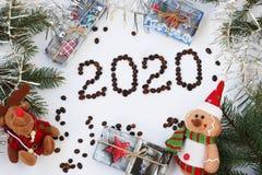 Предпосылка Нового Года с рождественской елкой, гирляндой, подарками и игрушками, надписью 2020 сделанной из кофейных зерен стоковые фото