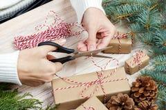 Предпосылка оборачивать подарка рождества Женские руки упаковывая подарок на рождество с красной лентой, взгляд сверху Концепция  Стоковые Фото