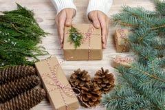 Предпосылка оборачивать подарка рождества Женские руки упаковывая подарок на рождество с белой лентой сатинировки, взгляд сверху  Стоковые Изображения RF