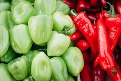 Предпосылка от перцы куча накаленных докрасна чилей и зеленые перцы закрывают вверх красивое сияющее текстура кучи перцев, стоковое фото rf