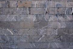 Предпосылка от серых мраморных блоков Стена грубого камня с черными рытвинами и белыми линиями стоковые изображения