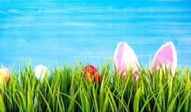 Предпосылка пасхи с красочными яйцами, зеленой травой и ушами bunnie стоковое фото