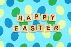 Предпосылка пасхи с красочными яйцами на голубой предпосылке Надпись счастливая пасха на деревянных блоках backhander бесплатная иллюстрация