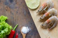 Предпосылка пищевого ингредиента Креветка, перцы, салат, соль, деревянная известка плиты или лимон на таблице Стоковые Фото