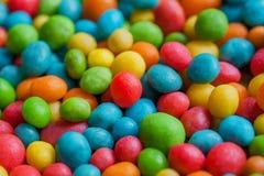 Предпосылка помадки конфеты сахара Confections в зеленом, желтом, красном цвете падают Яркая текстура и круглые формы изюминок Стоковые Изображения RF