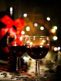 Предпосылка праздника с стеклами красного вина, красного вина и орнаментов рождества на деревянном столе Стоковые Фотографии RF