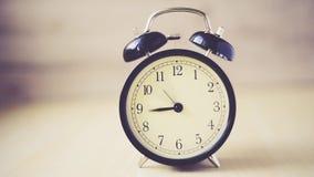 Предпосылка промежутка времени винтажная с ретро будильником на таблице акции видеоматериалы