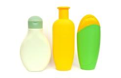 предпосылка разливает белизну по бутылкам шампуня Стоковые Фотографии RF