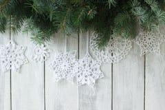 Предпосылка рождества или Нового Года с ветвями ели и связанными белыми снежинками на белой предпосылке Стоковые Фото