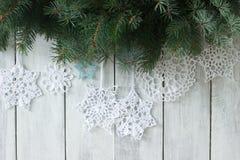 Предпосылка рождества или Нового Года с ветвями ели и связанными белыми снежинками на белой предпосылке Стоковые Фотографии RF
