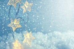 Предпосылка рождества и Нового Года сияющая, звезда гирлянды освещает Стоковое Фото