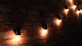 Предпосылка рождества - красная кирпичная стена с лампами, которые освещают вверх и идут вне акции видеоматериалы