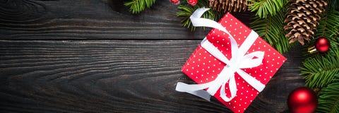 Предпосылка рождества с елью и красной коробкой присутствующими на темноте Стоковое фото RF
