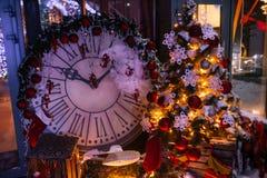 Предпосылка рождества с загоренными елью и камином, часами на доме стоковая фотография